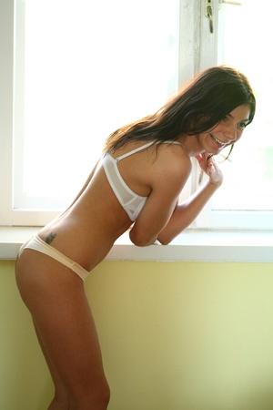 Shirtless girl in panties agains window photo