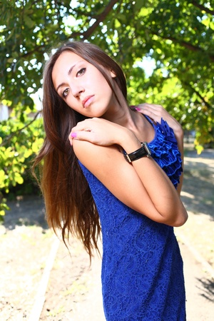 Portrait of a sexy young female in a park in blue dress Stock Photo - 11338924