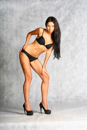sexy brunette in black bikini on the grey background Stock Photo - 12510951