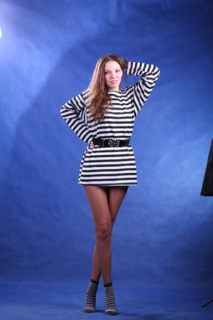 Young brunette lady in stripped dress posing on grey background photo