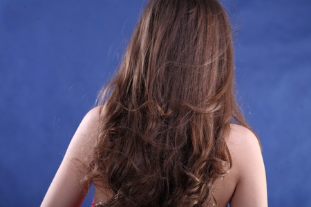 Rear view of beautiful brunette woman with long hair  on blue background photo