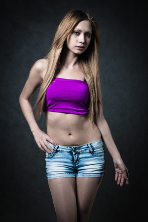 girl in shorts: blonde girl posind in studio in jeans shorts on dark background Stock Photo