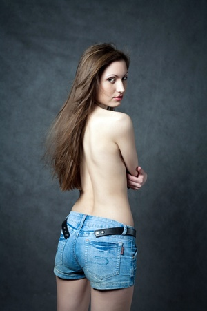 undressing woman: Isolated portrait of a beautiful and sexy young woman with a bare back.