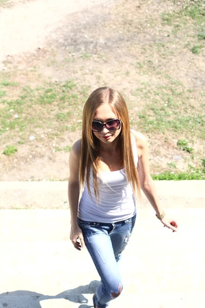 Blond woman in jeans and dark glasses standing on an outdoor summer patio photo