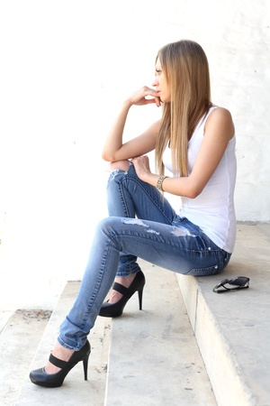Outdoor photo of pretty girl sitting on the floor in grungy setting. Stock Photo - 13318598