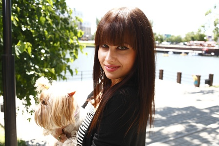 Beautiful brunette girl outdoors in summer with dog photo