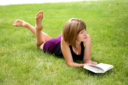 girl reading book outdoors laying on the green grass photo