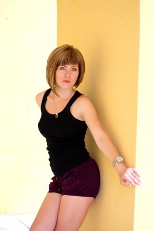 Stunning brunette beauty near yellow wall outdoors photo