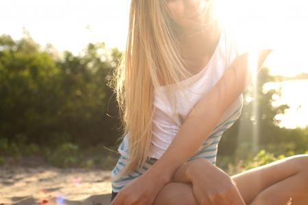 blond girl sitting near river against sun photo