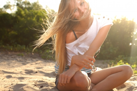 blond girl sitting near river against sun Stock Photo