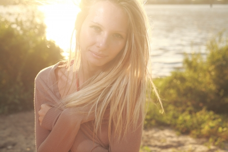 blond girl sitting near river against sun photo