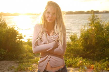 candid: blond girl near river against sun on sunset