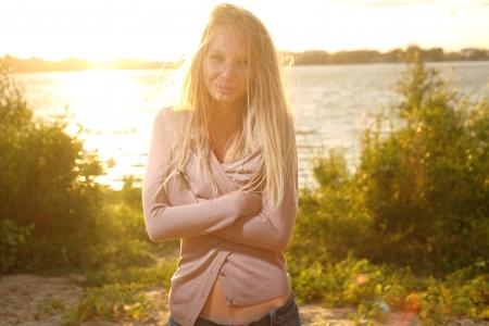 backlit: blond meisje buurt van de rivier tegen de zon op zonsondergang