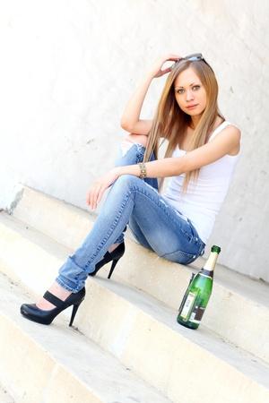 Leuke vrouwelijke zittend op de trap met een fles wijn