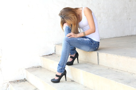 female sitting on the stairs in depression state photo