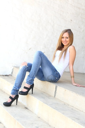 Outdoor photo of pretty girl sitting on the floor in grungy setting. photo