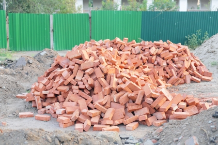 Lots of new red clay bricks lying outdoors photo