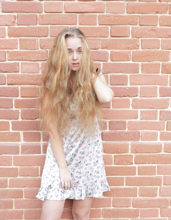 Attractive young blonde in wintage dress on the background of a brick wall. photo