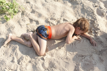 Portrait of happy little boy lying on the beach with his family in background while playing - Outdoors Stock Photo - 15238165