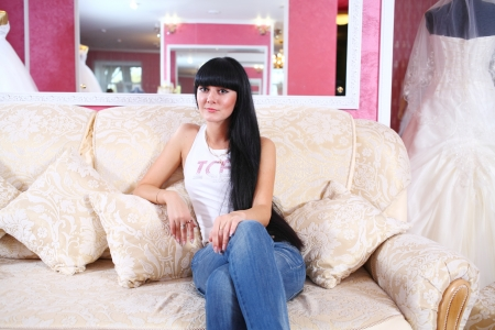 Beautiful young woman sitting on sofa, in jeans photo