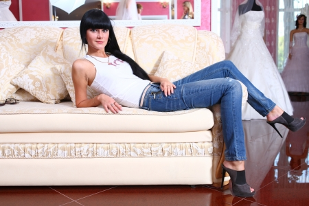 calm down: Beautiful young woman laying on sofa, wearing jeans Stock Photo