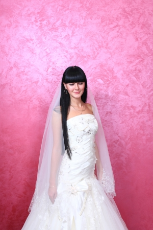 studio portrait of a happy beautiful brunette bride against red background photo