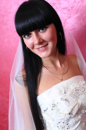 closeup portrait of a happy beautiful brunette bride against red background photo