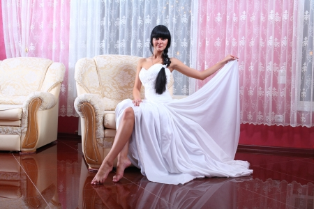 Beautiful bride in elegant wedding dress with long hair sitting in chair  photo