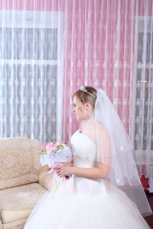 Happy bride with a bouquet of roses. Indoors photo