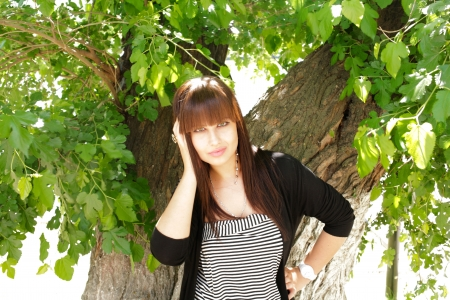 face in tree bark: Brunette fashion portrait in outdoors with natural expression