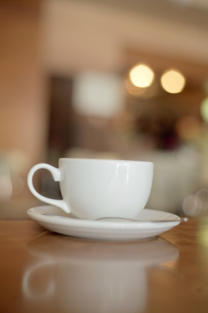 close up of  a delicious cup of coffee on wooden table. photo