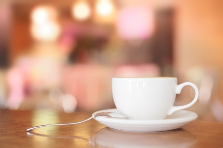 White Coffee Cup on brown wooden table with bokeh photo