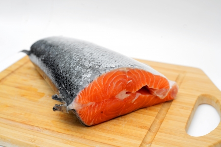 A piece of salmon in the fish section on a cutting board photo