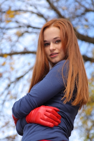 Close-up portrait of a beautiful red-headed girl posing outdoors photo