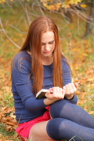 young, beautiful girl holding an open book, read background fall park Stock Photo - 15690302