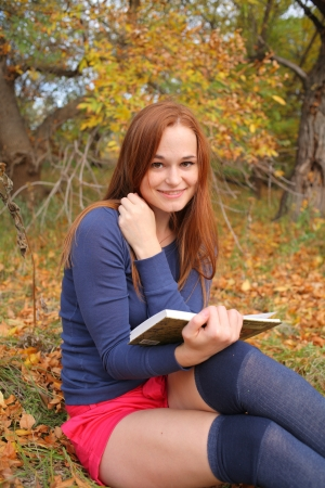 young, beautiful girl holding an open book, read background fall park Stock Photo - 15690304