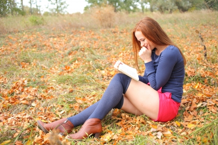 young, beautiful girl holding an open book, read background fall park Stock Photo - 15690331