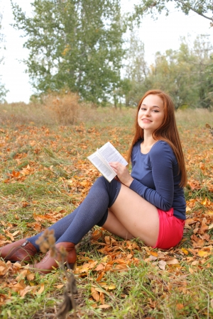 young, beautiful girl holding an open book, read background fall park Stock Photo - 15690335