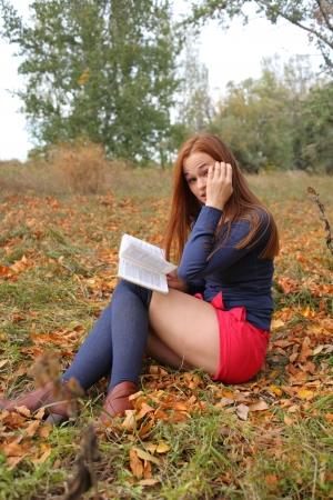 young, beautiful girl holding an open book, read background fall park