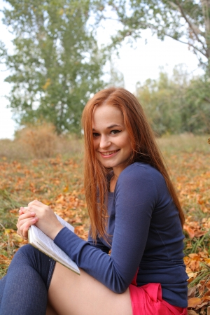 young, beautiful girl holding an open book, read background fall park Stock Photo - 15690295