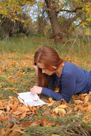 young, beautiful girl holding an open book, read background fall park Stock Photo - 15690307