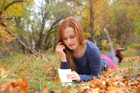 young, beautiful girl holding an open book, read background fall park Stock Photo - 15690297