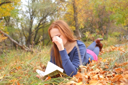young, beautiful girl holding an open book, read background fall park Stock Photo - 15690296