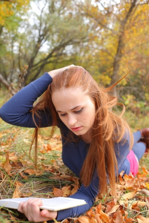 young, beautiful girl holding an open book, read background fall park photo