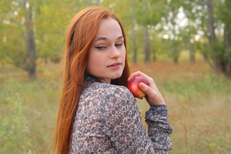 portrait of young woman holding red apple in hand outdoor photo
