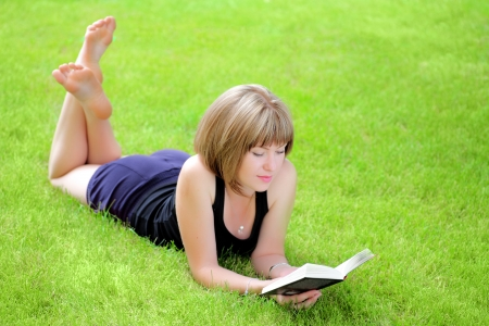 Beautiful young smiling woman laying on grass reading book, against green of summer park. photo