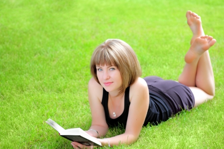 outdoor picture of lovely student girl with book on the fresh grass photo