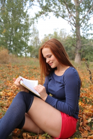 redhead young woman outdoors in the field reading in autumn park photo