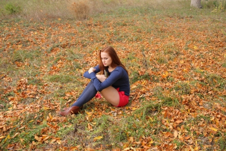 young redhead girl in blue clothes sitting  photo