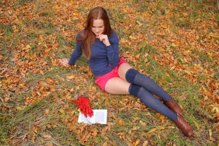 Young Woman  Leaning Book outdoors in autumn park photo